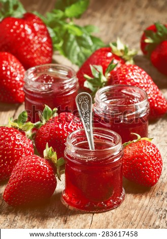 Fresh homemade strawberry jam with berries in small jars, selective focus - stock photo