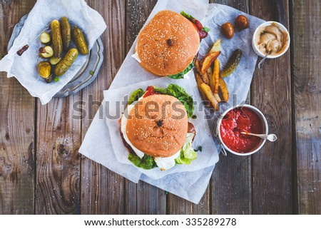 Fresh homemade two  burgers on dark serving board with spicy tomato sauce, vegetables  and marinated cucumber over dark wooden background. Top view - stock photo