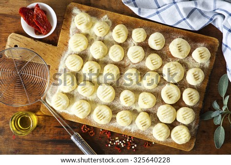 fresh homemade uncooked gnocchi filled with dried tomatoes on vintage wooden table . strainer for cooking and cutting board - stock photo