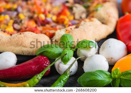 Fresh homemade vegetarian pizza with ingredients, overhead on wooden table - stock photo
