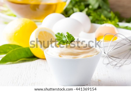 Fresh homemade white sauce Mayonnaise and ingredients eggs, lemon olive oil on white background - stock photo