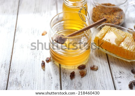 Fresh honey on wooden table - stock photo