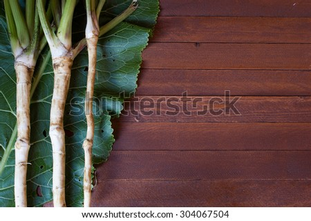 Fresh horseradish roots with leaves on wooden background - stock photo