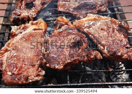 fresh hot bbq grill red beef meat steak ready on grid over charcoal with marks - stock photo