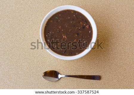 Fresh hot black bean soup in white bowl on kitchen table - stock photo