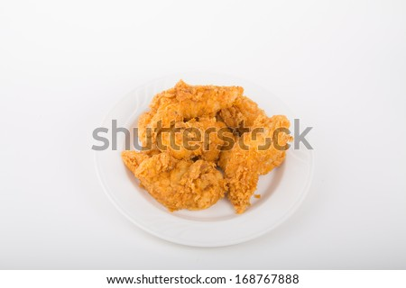 Fresh, hot, fried chicken strips on a white plate - stock photo