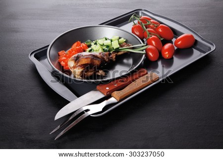 fresh hot grilled turkey drumstick leg with vegetables on black metal plate over wooden table - stock photo