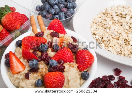 Fresh, hot oatmeal in a bowl garnished with cinnamon, strawberries, blueberries and dried cranberries with oats, strawberries and blueberries in the background - stock photo
