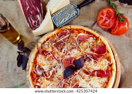 Fresh hot pizza with Parmesan Cheese, jerked meat, Basil and tomatoes - stock photo
