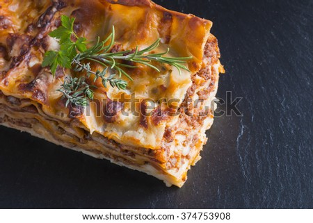 fresh hot steaming lasagna pasta served on wooden table and slate plate - stock photo