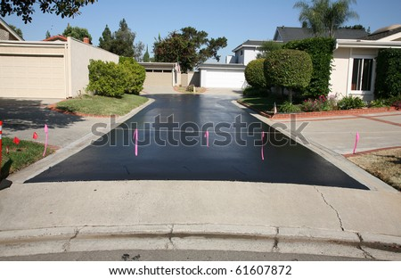fresh hot tar aka black top on an ashphalt driveway in a neighborhood