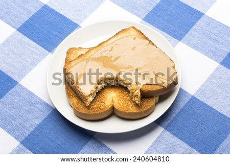Fresh, hot toast spread with peanut butter sits with a bite taken out of it during mealtime.  - stock photo