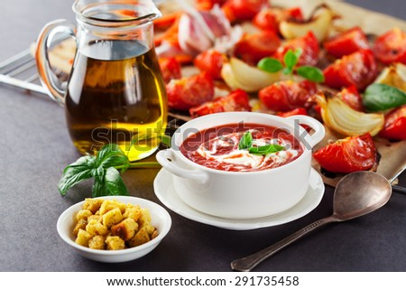Fresh hot tomato soup with smoked tomatoes, basil and olive oil on a dark background, selective focus - stock photo