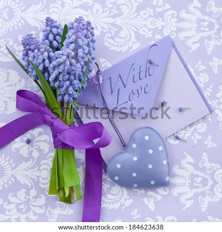 Fresh hyacinths  with ribbon and little letter on purple - stock photo