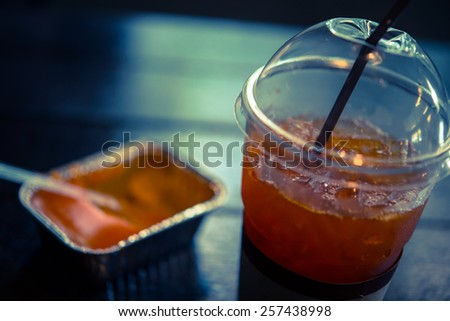 Fresh ice tea in plastic glass and orange cake in cold color toned effect style picture - defocus - stock photo