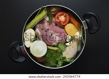 Fresh ingredients chicken and beef soup in a large pot - stock photo