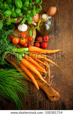 Fresh ingredients for cooking in rustic setting: tomatoes, basil, olive oil, garlic and onion - stock photo
