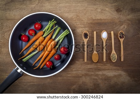 Fresh ingredients for cooking in rustic setting: tomatoes, carrots. - stock photo