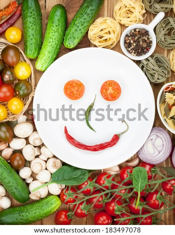 Fresh ingredients for cooking: pasta, tomato, cucumber, mushroom and spices over wooden table background and plate with smile - stock photo