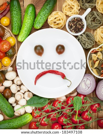 Fresh ingredients for cooking: pasta, tomato, cucumber, mushroom and spices over wooden table background and plate with sad smile - stock photo