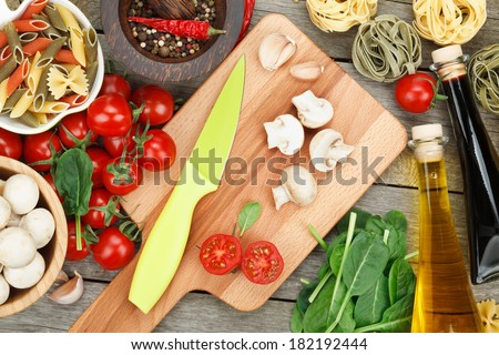 Fresh ingredients for cooking: pasta, tomato, mushroom and spices over wooden table background - stock photo