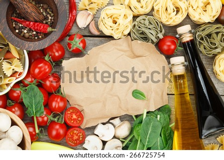 Fresh ingredients for cooking: pasta, tomato, mushroom and spices over wooden table background and paper with copy space - stock photo