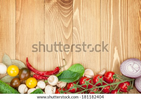Fresh ingredients for cooking: tomato, cucumber, mushroom and spices over wooden table background with copy space - stock photo