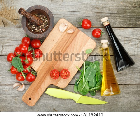 Fresh ingredients for cooking: tomato, salad and spices over wooden table background with copy space - stock photo