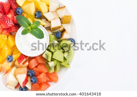 fresh ingredients for fruit salad and natural yoghurt on plate, top view, closeup - stock photo