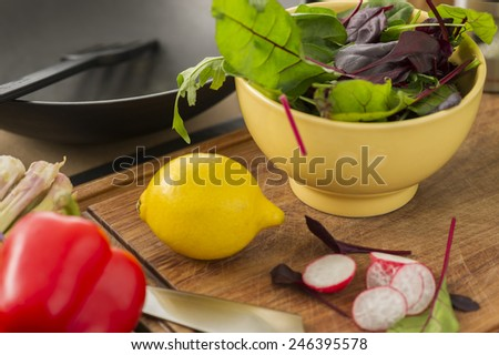 Fresh ingredients for making a salad on a chopping board in the kitchen with sliced radish, rocket, baby spinach and herbs in a bowl, red bell pepper and a ripe yellow lemon - stock photo