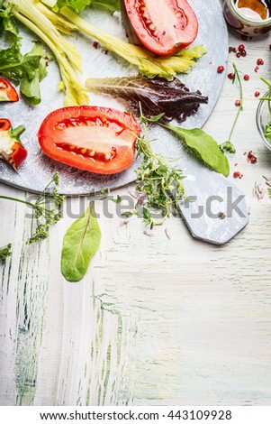Fresh ingredients for tasty salad on round white cutting board and wooden background, top view, place for text - stock photo