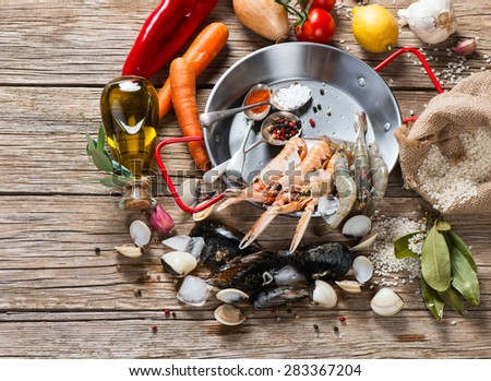 Fresh ingredients on the wooden board for preparation of seafood paella. Concept of cooking. - stock photo