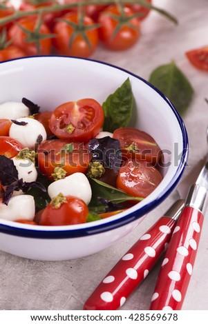Fresh italian caprese salad  mozzarella, cherry tomatoes and pesto sauce in enamel bowl. Selective focus - stock photo