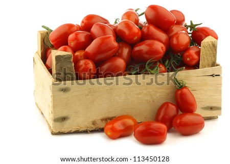 fresh italian cherry tomatoes on the vine in a wooden crate on a white background