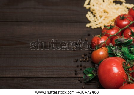 Fresh Italian food on wooden background. Ingredients: pasta, tomatoes, mushrooms, herbs, vegetables and spices
