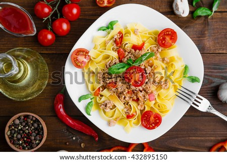 Fresh Italian Pasta Fettuccine with raw pepper, basil And Garlic On Brown Wooden Background