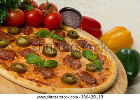 Fresh italian pizza with salami and jalapeno on wooden board with vegetables, close up