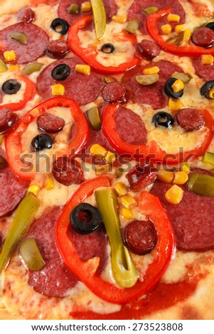 Fresh Italian pizza with salami, sausage, frankfurters, red pepper, cucumber, corn, green and black olives close-up, selective focus, macro - stock photo