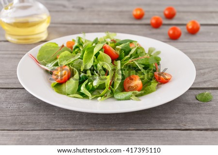 Fresh Italian salad in a white plate on a wooden table. Healthy food