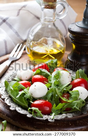 Fresh italian salad with mozzarella cheese, tomato and rucola on vintage old metal plate. Healthy food. Selective focus. - stock photo