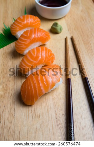 Fresh japanese salmon sushi with chopsticks, wasabi and sauce on wood cut board - stock photo