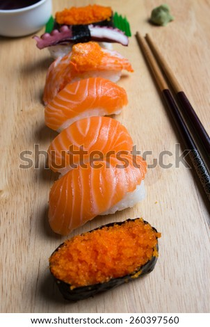 Fresh japanese sushi with chopsticks, wasabi and sauce on wood cut board - stock photo