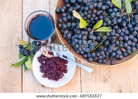 Fresh juice and jam of ripe black chokeberry (Aronia melanocarpa) in glass and berry in pot on wooden background