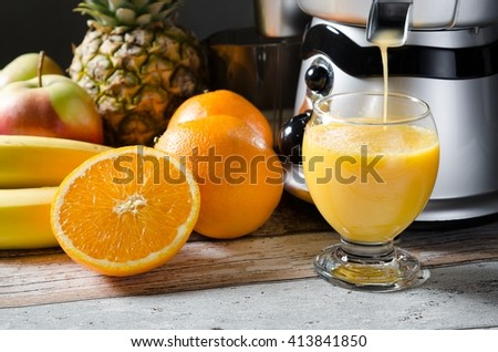 Fresh juice and juicer. Photo on wooden background with lot of fruits - stock photo