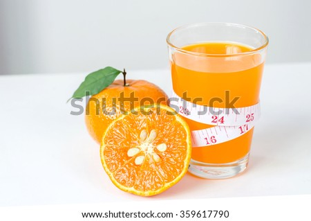 Fresh juice in glass white measuring tape and slide orange on white background, diet concep - stock photo