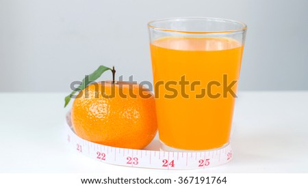 Fresh juice in glass with measuring tape and slide orange on white background, diet concep - stock photo