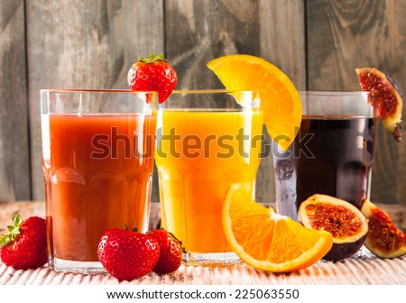 Fresh juice, mix fruits orange, strawberry, lime, and ficus drinks on wood plants background. - stock photo