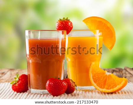 Fresh juice, mix fruits, strawberry and orange drinks with nature green background - stock photo