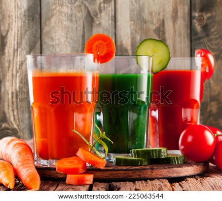 fresh juice, mix vegetable, tomato, cucumber and carrot drinks with wood plants background. - stock photo