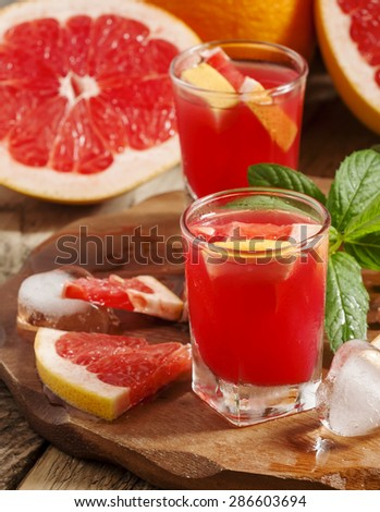 Fresh juice of red grapefruit pulp, ice and citrus slices, selective focus - stock photo